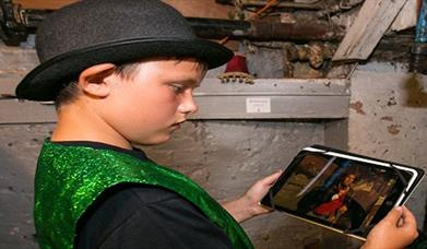 boy in bowler hat and glittery green waistcoat looking at an ipad screen