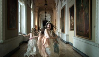 girls in period costumes dancing down a corridor of a grand house