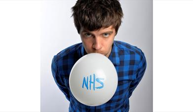 Ed Patrick blowing up a balloon with NHS written on it.