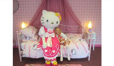 young girl on bed with Hello Kitty.
