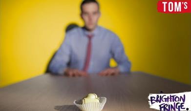 Man out of focus sitting across a table with a Fondant Fancy cake in the foreground