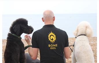 Man wearing Bone T. Shirt with Bone Idol logo on the rear with two dogs.