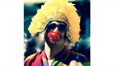 Man with yellow headress and red rose in his mouth