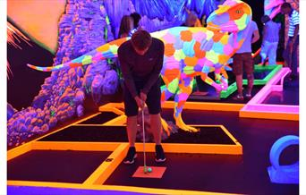 Man taking a putt with fluorescent Therapod dinosaur behind him!
