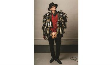 Simon Munnery dressed in beer cans and a plastic pig head