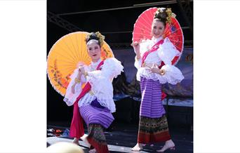 Thai ladies in traditional dress with parasols