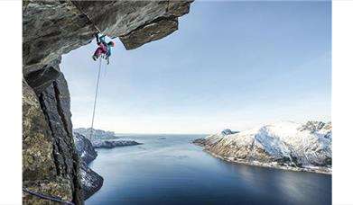 climber on a cliff face hanging over a lake!