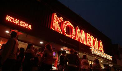 Komedia exterior at night with neon sign lit up