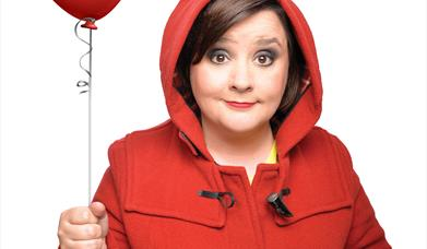 Susan Calman in red duffel coat and red balloon